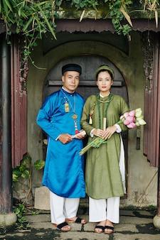 연꽃을 들고 전통 아오자이 드레스를 입은 진지한 젊은 베트남 부부