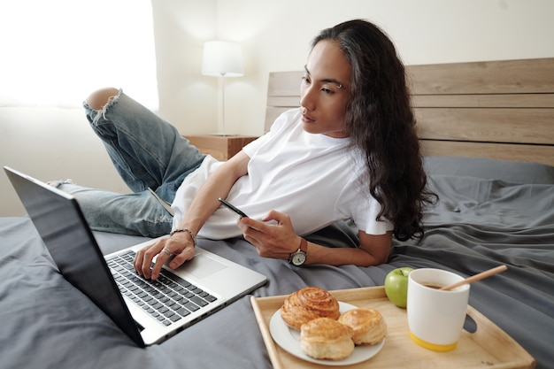 Serious young vietnamese man with wavy hair lying on bed with tray with buns, coffee and apple and using modern devices in bedroom