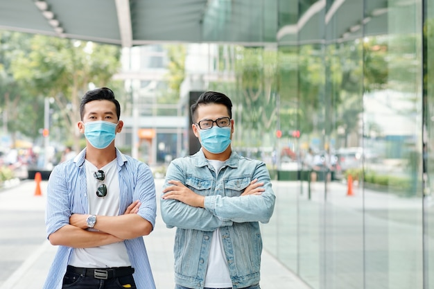 Serious young vietnamese men in medical masks standing in the street with arms folded and looking at camera