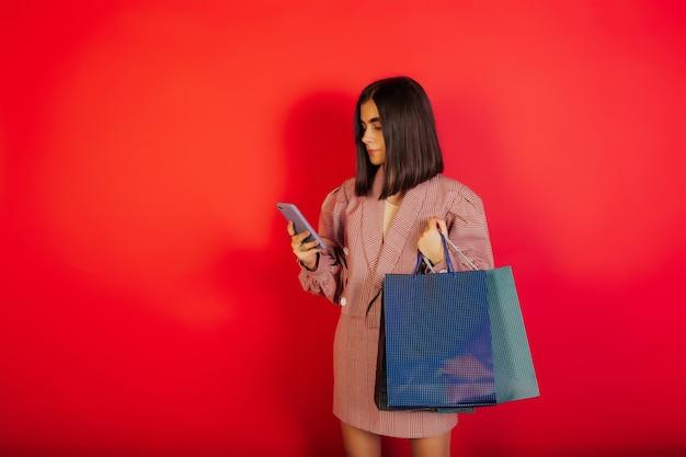 真面目な若い女性が携帯電話でオンラインショッピングをし、赤い表面にカラフルな買い物袋を持っています。