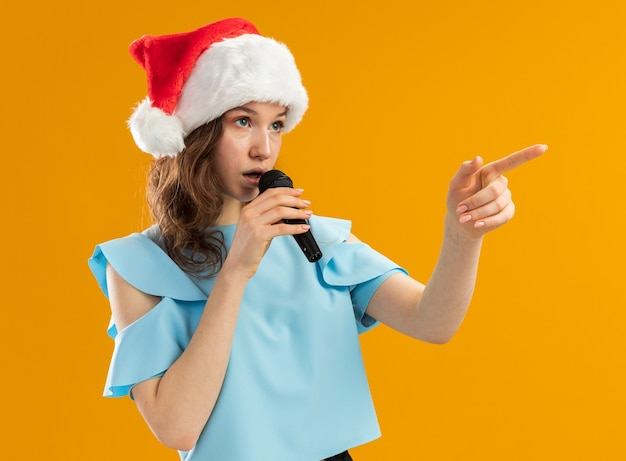 Serious young woman in blue top and santa hat speaking to microphone pointing with index finger to the side