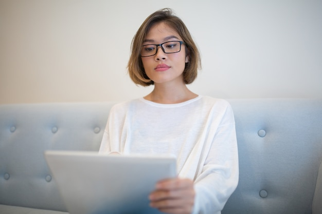 Serious young woman browsing on tablet computer on sofa