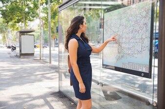 バスステーションで地図を忠実な若い女性のコンサルティング