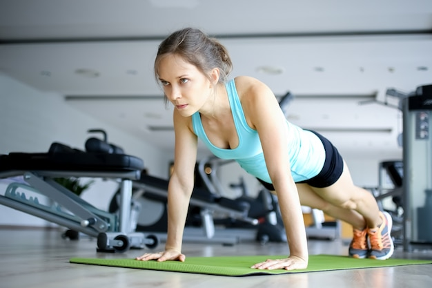 Serious young woman doing push-ups on mat in gym