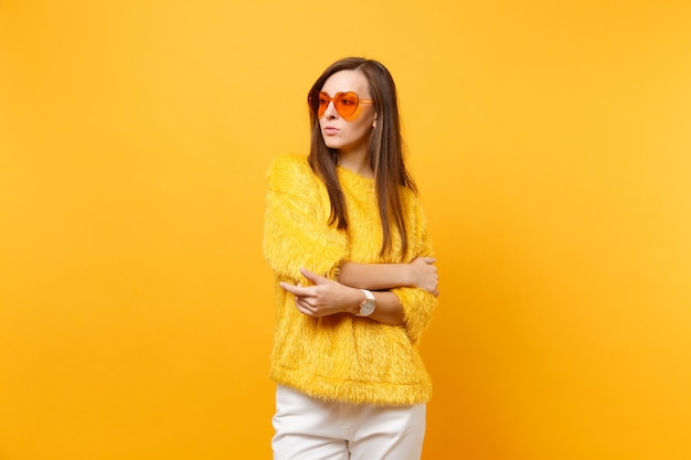 Serious young woman in fur sweater and heart orange eyeglasses looking aside, holding hands folded isolated on bright yellow background. people sincere emotions, lifestyle concept. advertising area.