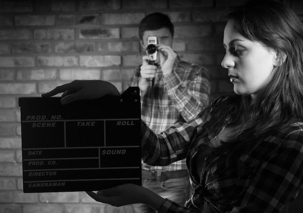 後ろに若い男性の写真家とカチンコを保持している深刻な若い女性。モノクロで撮影。