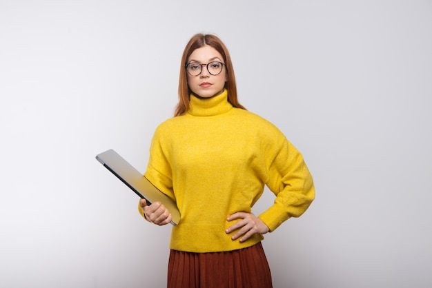 Serious young woman holding laptop