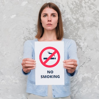 Serious young woman holding social message paper of no smoking