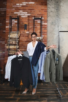 Serious young woman holdning several hangers with man clothes in modern appartments interior