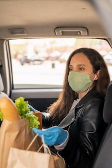Серьезная молодая женщина в тканевой маске сидит с сумками на заднем сиденье автомобиля такси, возвращаясь домой после покупок в супермаркете во время пандемии