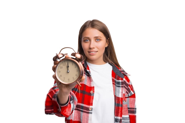 Serious young woman is showing an alarm clock to the camera.