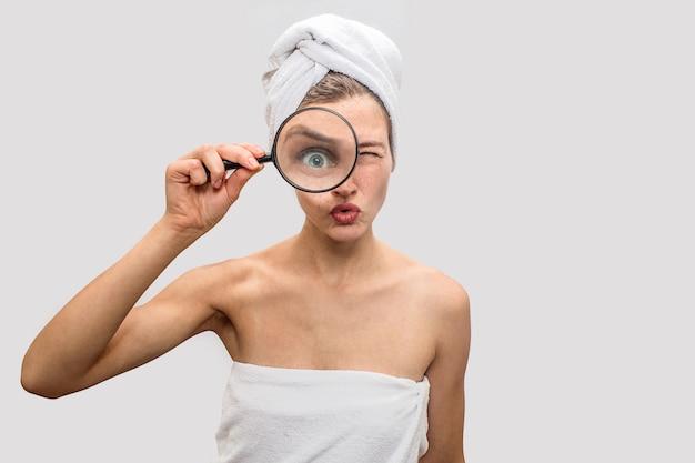 Серьезная молодая женщина смотрит через петлю. она удивляется. модель держит его в правой руке. ее тело и волосы покрыты белыми полотенцами.