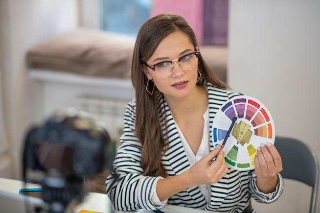 Серьезная молодая женщина, указывая на цвет, рекомендуя выбрать его