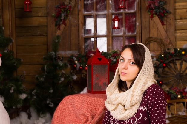 Серьезная молодая женщина надевает зимний шарф на голову, глядя в камеру. захвачено в доме с различными рождественскими украшениями.