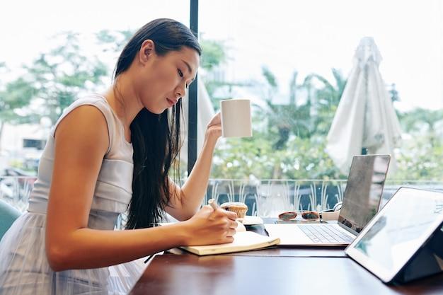 Серьезная молодая женщина сидит за столом в кофейне, пьет кофе и пишет планы на день в блокноте