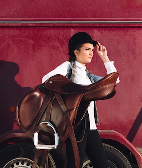 Serious young woman sitting outdoors and holding saddle