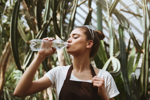 Serious young woman standing in greenhouse drinking water.