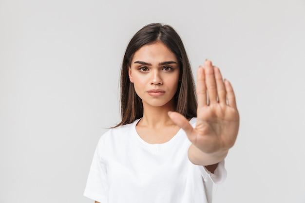 真面目な若い女性が白で孤立して立って、停止ジェスチャーを示しています