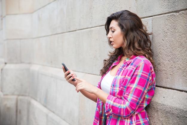 電話でネットサーフィンをしている真面目な若い女性