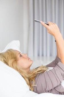 Serious young woman taking selfie with smartphone