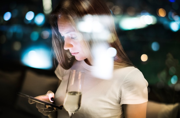 Serious young woman using a smartphone at a rooftop bar in the evening