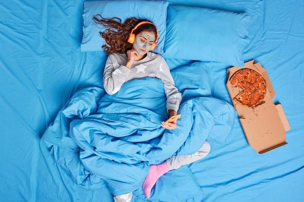 Серьезная молодая женщина смотрит фильм онлайн через смартфон, использует стереонаушники, накладывает глиняную маску на лицо, чтобы уменьшить морщины, проводит ленивый день дома, лежа в постели, ест вкусную пиццу, носит пижаму