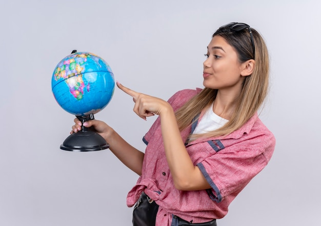 A serious young woman wearing red shirt pointing at globe with index finger on a white wall