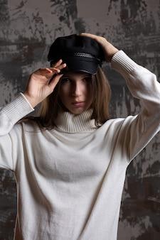 真面目な若い女性は彼女の顔に影を付けてスタジオでポーズをとるキャップと白いニットのセーターを着ています