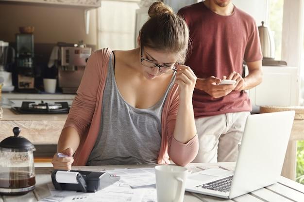 Grave giovane donna con i capelli panino con gli occhiali guardando attraverso le finanze
