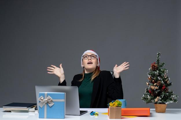 Grave giovane donna con cappello di babbo natale e occhiali seduti a un tavolo con un albero di natale e un regalo su di esso su sfondo scuro