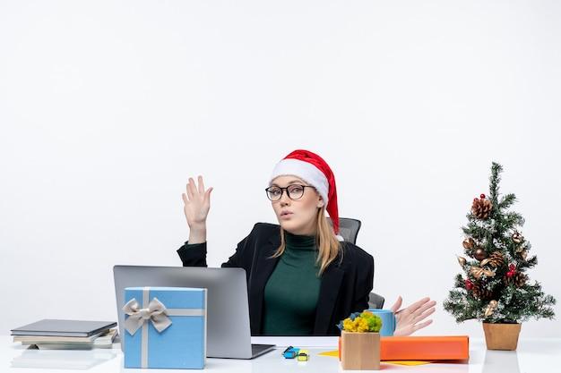 Grave giovane donna con cappello di babbo natale seduto a un tavolo con un albero di natale e un regalo su di esso su sfondo bianco