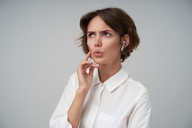 흰 셔츠와 이어폰을 착용하고 눈썹을 찌푸리고 입술을 접고 서있는 짧은 갈색 머리를 가진 심각한 젊은 여성