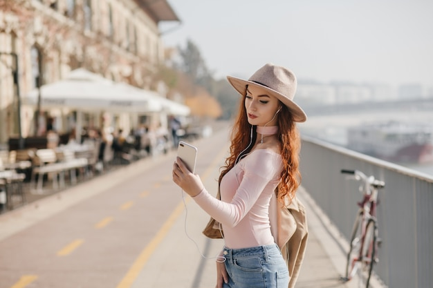 Serious young woman with wavy ginger hair making selfie