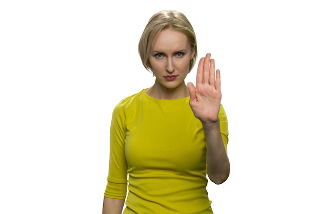 Serious young woman in yellow turtleneck making stop gesture with her palm