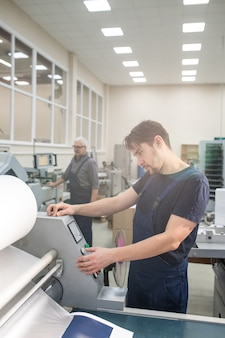 Serious young worker in overall standing at printing machine and choosing copy amount on control panel