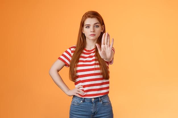 진지해 보이는 자신감 넘치는 용감한 빨간 머리 소녀는 불법 행위를 금지하는 자유를 위해 싸우는 증오자를 반대합니다 ...
