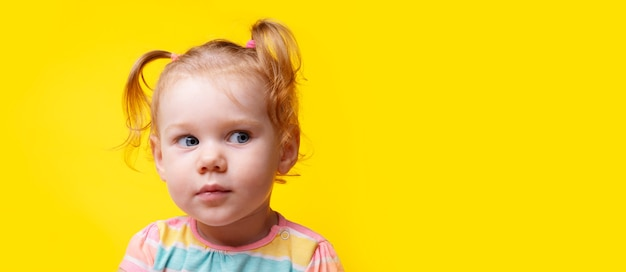 Seriously baby girl looking side on empty yellow background, panoramic layout with space for text