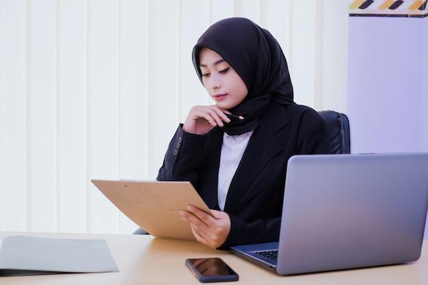 Серьезно деловая молодая женщина, держащая финансовый документ в офисе