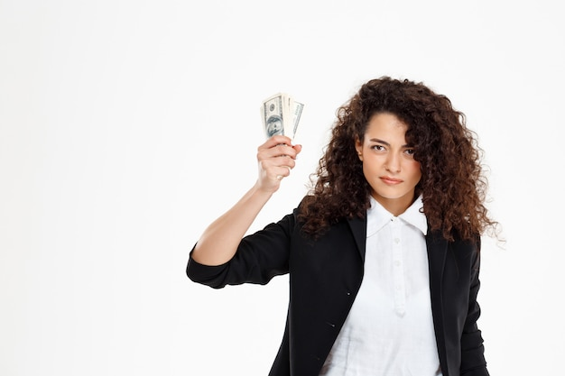 Seriously curly business girl holding money
