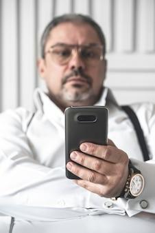 白いシャツを着た真剣に不機嫌なビジネスマンが電話を見ている