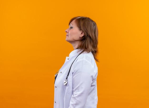 真剣に探している中年女性医師医療ローブとコピースペースと孤立したオレンジ色の壁に縦断ビューで聴診器立って身に着けています。