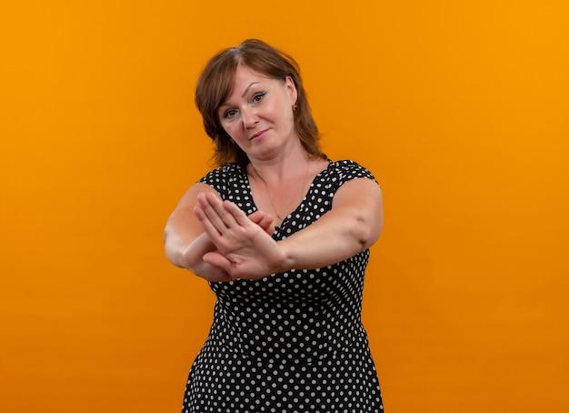 コピースペースを持つ孤立したオレンジ色の壁に停止ジェスチャーをしている真剣に探している中年女性