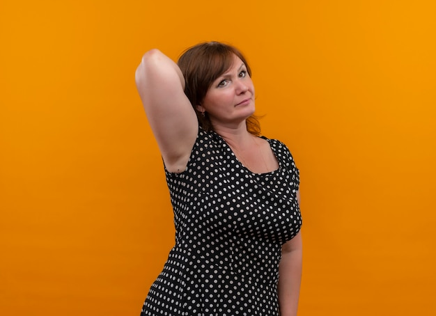 真剣に探している中年の女性の後ろに手を置くコピースペースと孤立したオレンジ色の壁