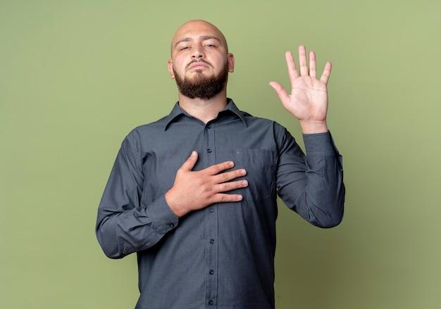 Серьезно выглядящий молодой лысый человек из колл-центра смотрит вперед и делает жест обещания, изолированный на оливково-зеленой стене