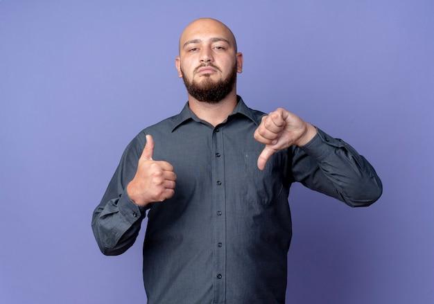 Серьезно выглядящий молодой лысый человек из колл-центра показывает большие пальцы руки вверх и вниз, глядя вперед, изолированную на фиолетовой стене
