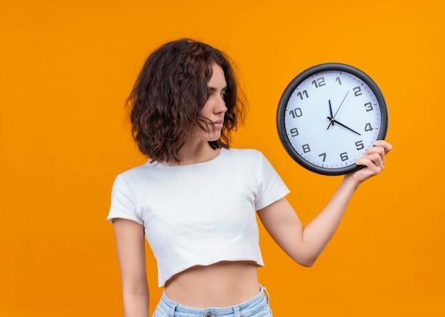時計を押しながらコピースペースで孤立したオレンジ色の壁にそれを見て真剣に探している若い美しい女性