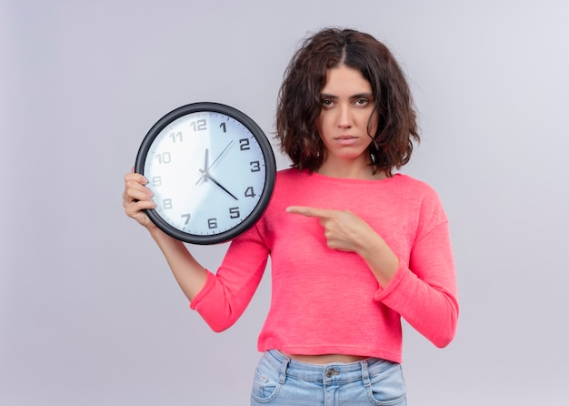 Seriamente guardando giovane bella donna che tiene orologio e indicandolo sulla parete bianca isolata
