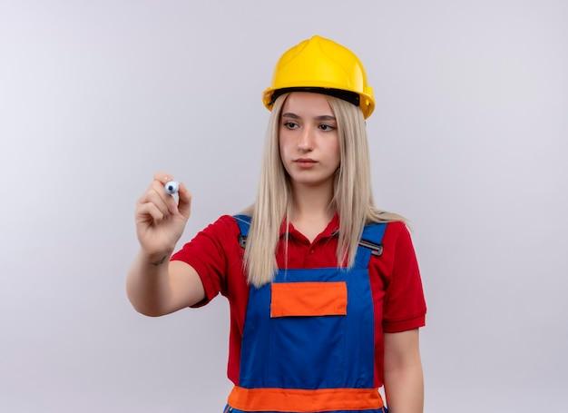 Ragazza bionda giovane del costruttore dell'ingegnere seriamente alla ricerca nella scrittura uniforme con l'indicatore sullo spazio bianco isolato