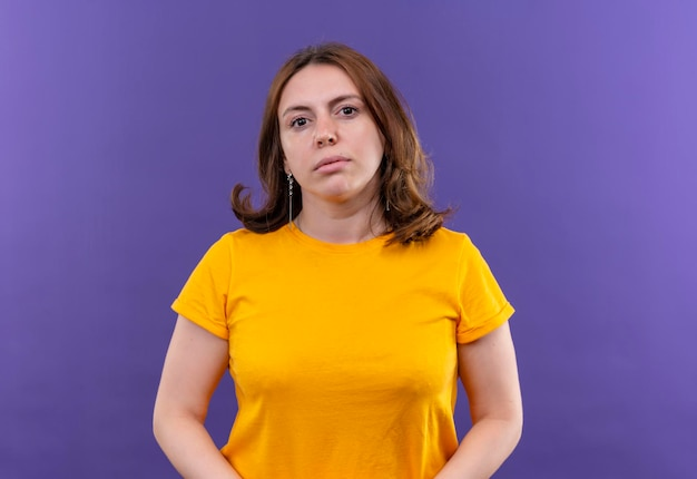 Seriously looking young casual woman looking  on isolated purple space with copy space