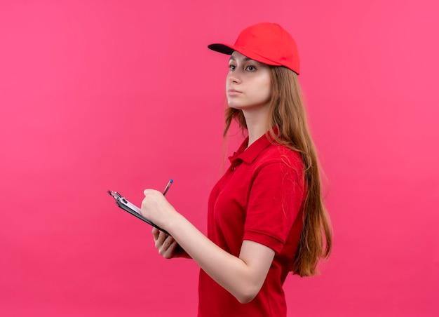 コピースペースと孤立したピンクのスペースの縦断ビューで立っている左側を見てクリップボードに書いている真剣に探している若い配達の女の子